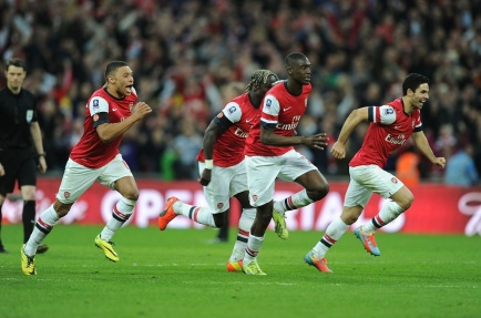 The Gunners rush to the spot to celebrate after defeating Wigan on penalties in the FA Cup Semifinal at Wembley.